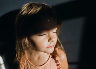 Young girl with eyes closed in sunlight