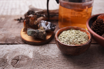 Herbal tea, homeopathy, alternative medicine, occult ritual concept/ Dry leaves in ceramic cup, stones, teapot on vintage wooden background, witchtable closeup