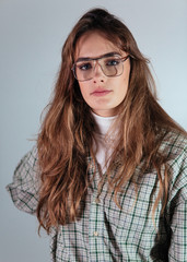1980's womans studio portrait with era specific steel rimmed eyeglasses, turtleneck and checked shirt.