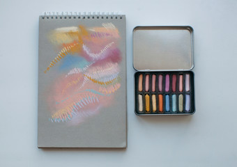 Metal box with assorted soft pastels and notebook with abstract drawing made with it