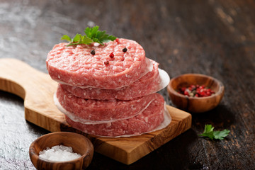 Raw Ground beef meat Burger steak cutlets  on dark wooden background. Wall mural