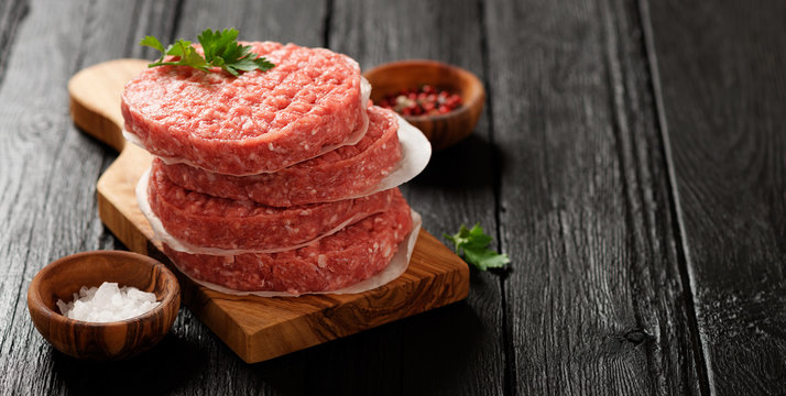 Raw Ground beef meat Burger steak cutlets  on dark wooden background.