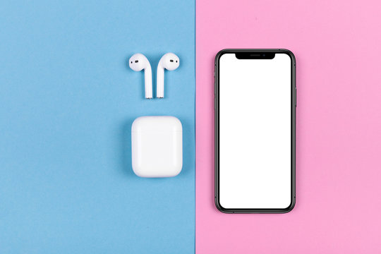 Kyiv, Ukraine, 2018-10-19. Top view of iphone XS and Apple AirPods on pink and blue background.