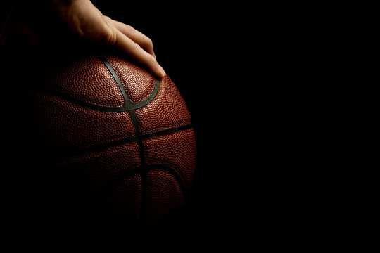 Man's One Hand Palming Leather Basketball Isolated On Black Background, Room For Text