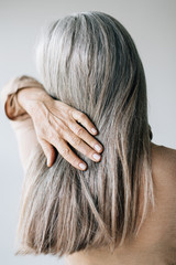 Back view of a senior woman with grey long hair.