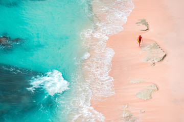 Woman surfing at wild tropical beach