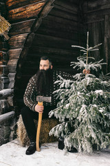 Good-Looking Bearded Man in Norwegian Knitwear Holding Axe and C