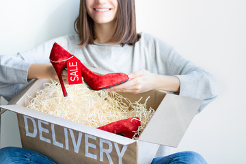Young female woman adult customer buyer smiling received purchased new red high heels with sale label in delivery box ordered in internet online fashion shop store in black friday holiday at home.