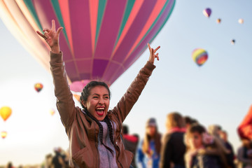 Excited, happy young woman at a balloon festival
