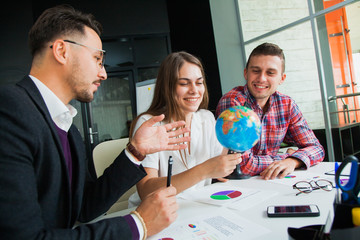 Group of three young people with globe choose country to travel to.