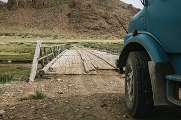 camping truck in front of a derelict wooden bridge in mongolian steppe