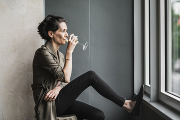 Short dark haired woman with a glass of white wine