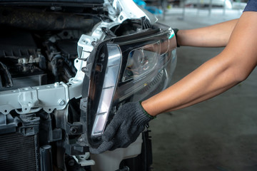 Mechanic changing car headlight in a workshop