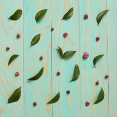 Blue wooden background decorated green leaves, pink flowers