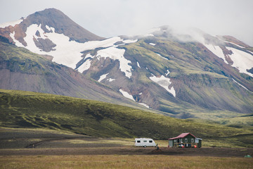 A mountain landscape with trailer and house