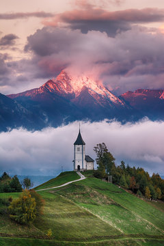 Beautiful sunrise landscape of church Jamnik in Slovenia with cloudy sky