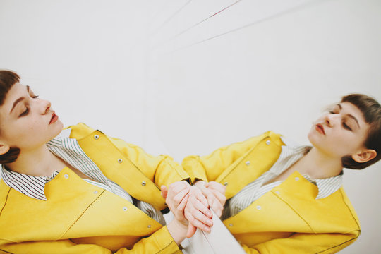 Stylish model in yellow looking in mirror