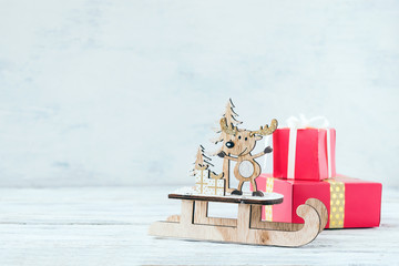 Christmas holiday festive theme with wooden cute reindeer on sled, red gift boxes on white rustic background. Christmas composition decoration with reindeer santa helper. xmas  gift concept copy space