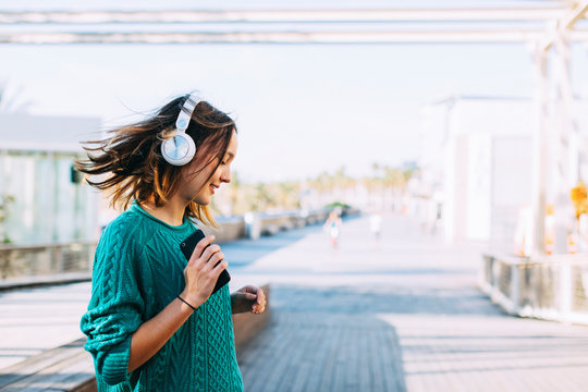 Teenager dancing listening music on the street.