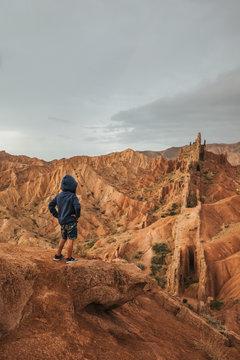 little boy standing in rugged bizzare mountain landscape, kyrgyzstan