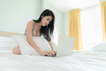 woman and laptop in bedroom on white bed