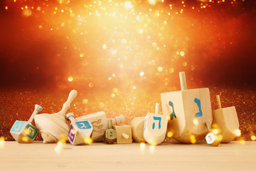 Banner of jewish holiday Hanukkah with wooden dreidels (spinning top) over glitter shiny background.