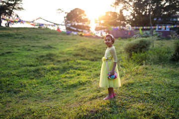 Smiling little girl standing in the field at sunset