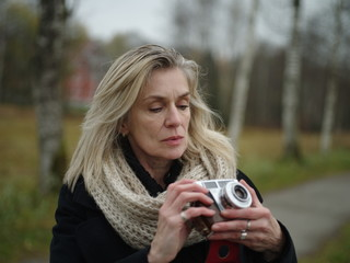 Stylish woman posing in park with camera