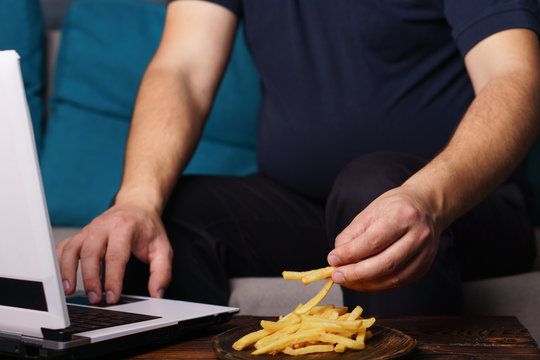 lack of physical activity, remote work, laziness, homebody. Lonely man watching series at laptop drink beer eat junk food