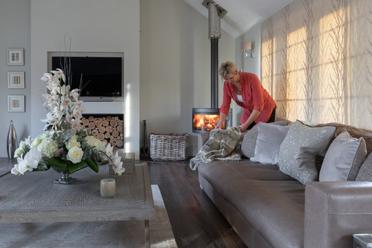 Interior designer preparing a sitting room of a modern house. Flower arrangement on a table in foreground.
