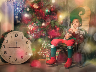 Caucasian boy in a suit of the magic gnome sits in a rocking-chair, holds in hand a red box with gifts. On a background the New Year tree is decorated with toys and fires, on hours time of 15 minutes