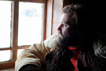 man in traditional winter costume of peasant medieval age in russian house