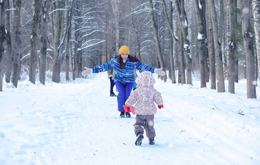 Kid playing in a winter park and have fun with family