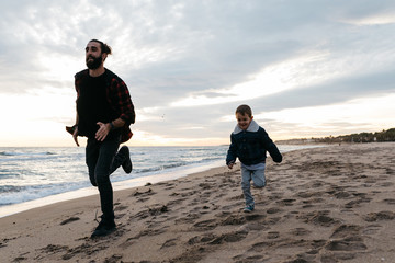 Content kid running on beach with dad
