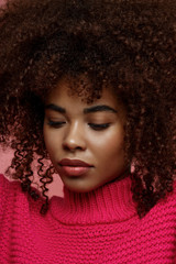 Portrait of a young African American afro woman in pink studio looking down