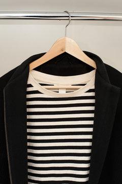 Black coat on a rail with stripe shirt