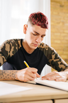 Young man writing in notepad