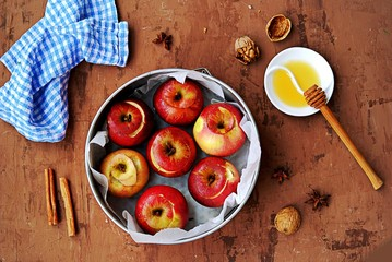 Fresh organic apples prepared for baking, with honey, walnuts and spices in a round baking dish on a brown background. Healthy dessert concept.