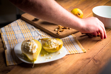 Backstage with a shot of a pear with cottage cheese, nuts, cinnamon and honey on a wooden, subject table. The hands of the photographer in the frame. Creating a photo