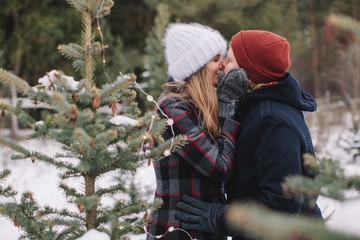 Happy young couple kissing near the pine outdoors