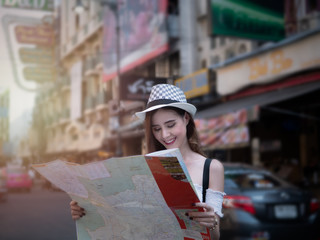Cheerful woman wanderer with trendy look searching direction on location map in city centre. Happy female traveler and tourist concept,  Khao San Road walking street at Bangkok, Thailand