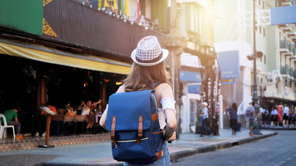 Back side of Young traveling women with backpack in city centre are walking Khaosan Road walking street in evening at Bangkok, Thailand. Happy female traveler and tourist concept.