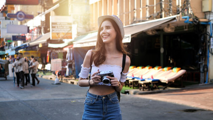 Beautiful young caucasian taking photos in city centre are walking Khaosan Road walking street in evening at Bangkok, Thailand. Happy female traveler and tourist concept.