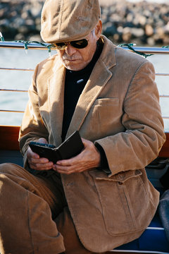 Senior Asian man looking at his phone on a classic wooden boat.