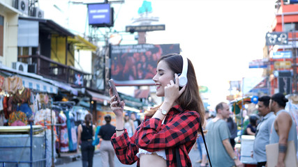 Beautiful young woman caucasian listening to music and walking street in evening at Bangkok, Thailand.