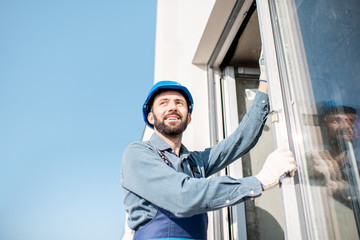 Workman in uniform mounting windows checking the level on the white building facade