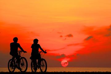 silhouette couple ride bike on sunrise