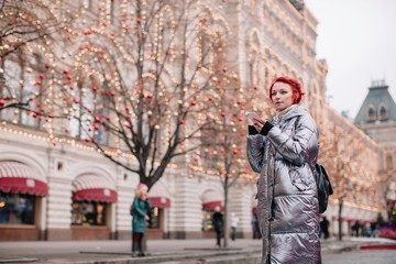 Tourist young fashionable woman standing near the GUM Moscow in winter time