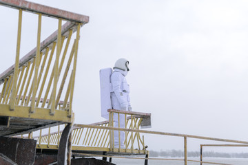 Astronaut standing on river pier in winter