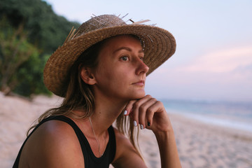 young woman in a swimsuit and hat sits on the ocean coast looking into the distance, thinking